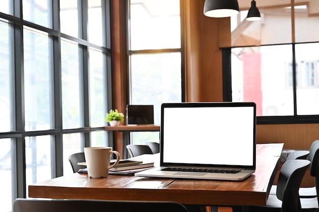 木製の机と作業テーブルの上のラップトップコンピューター。