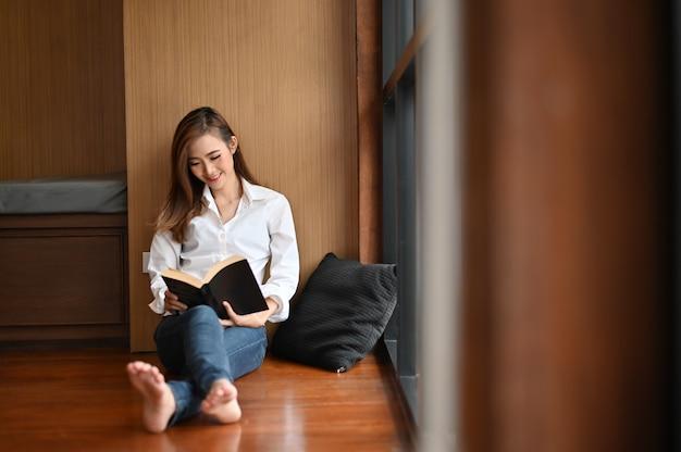 床に座って本を読む女性。