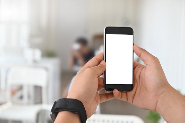 Крупным планом руки с помощью макета мобильного телефона.