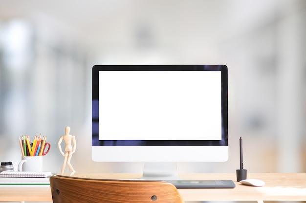 Офисное пространство с компьютером на деревянном столе и деревянном стуле.