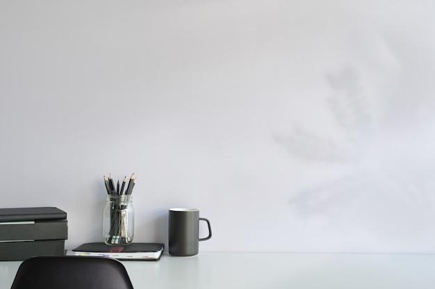 ワークスペースデスクのモックアップとスペースブックのコピー、黒い椅子と白い机の上のコーヒーと鉛筆。