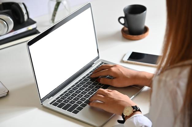 女性のオフィスの机の上のモックアップのラップトップコンピューターを使用して