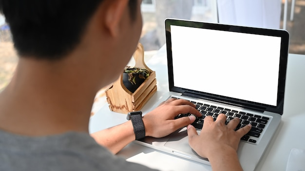空の画面でモックアップのラップトップコンピューターを使用している人。