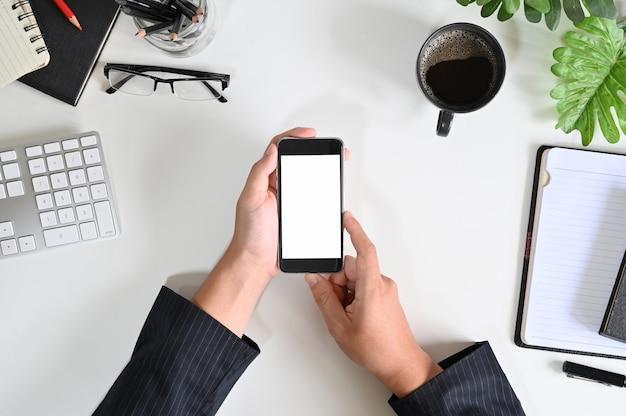 トップビューの実業家が事務机の上のモックアップのスマートフォンを使用して手します。