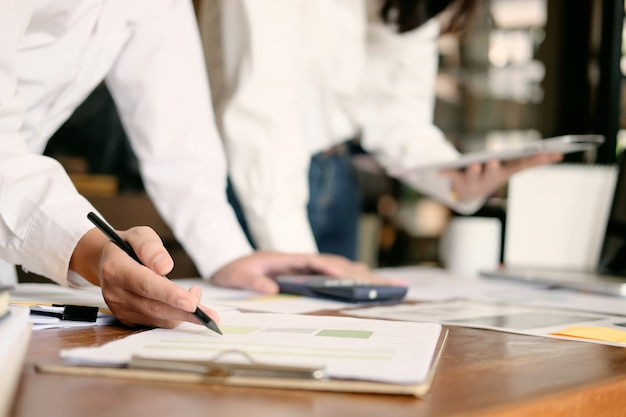 Бизнес-группа, работающая с финансовыми бумажными данными на офисном столе со старинным тоном.