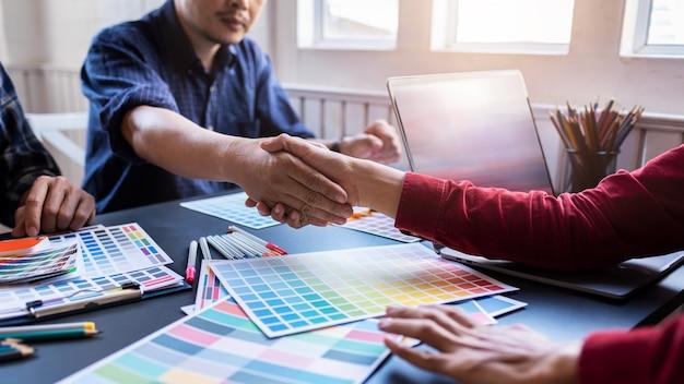 アジアのデザイナーのグループは、完成した製品の色を選択した後、会議後に握手をしました。