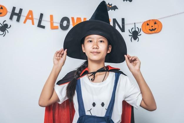 部屋で遊ぶアジアの女の子の魔女の衣装ハッピーハロウィン
