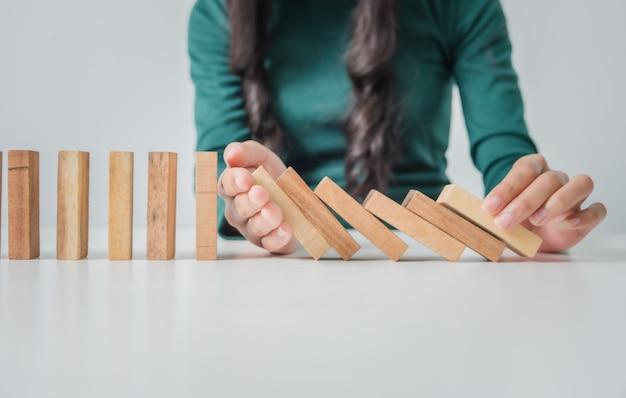 Молодая женщина останавливая деревянный блок