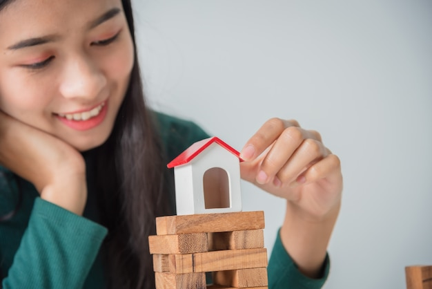 Игра молодой бизнес-леди азиатская с деревянными блоками и игрушечным домом