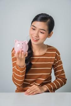 Молодая азиатская женщина с копилками