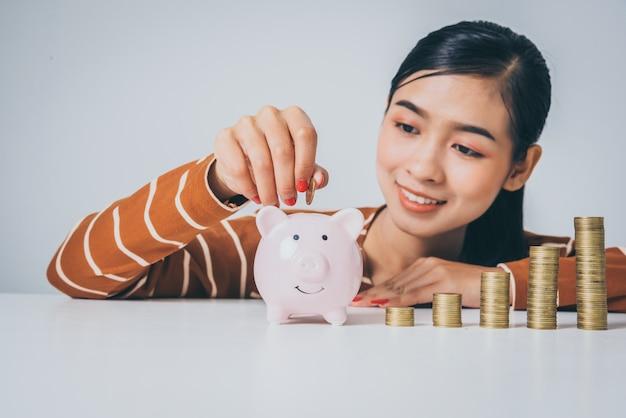 Молодая азиатская женщина с стогом монеток и копилки