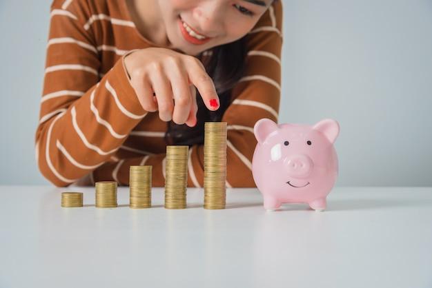 コインと貯金箱のスタックを持つ若いアジア女性