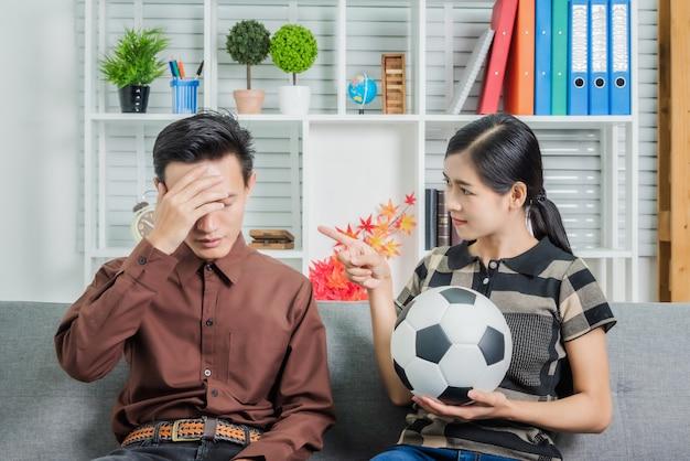 彼らのチームによって悲しい気持ちでサッカーの試合を見て若いアジアのカップルは試合に負けます。