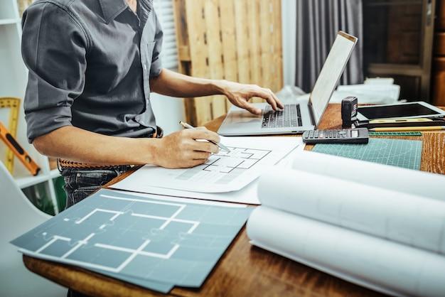 Человек архитектора работая с бумагой и светокопиями для концепции эскиза плана нового строительства строения архитектурноакустической.