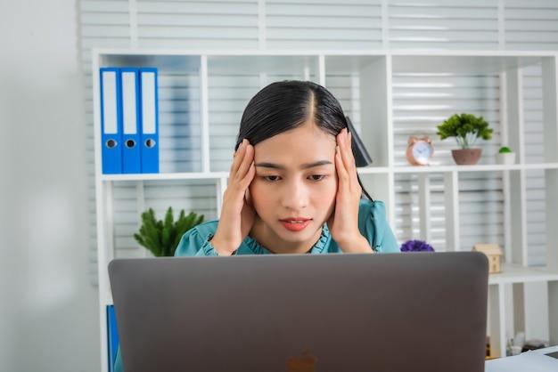 Молодая женщина бизнес-леди устала усердно работать дома страдает от ужасной мигрени в комнате.