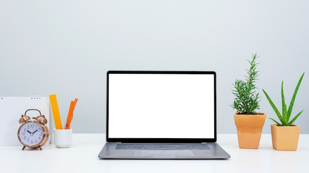 空白のノートパソコンの画面、時計、空白のカレンダーを持つスタイリッシュなオフィスのワークスペース。