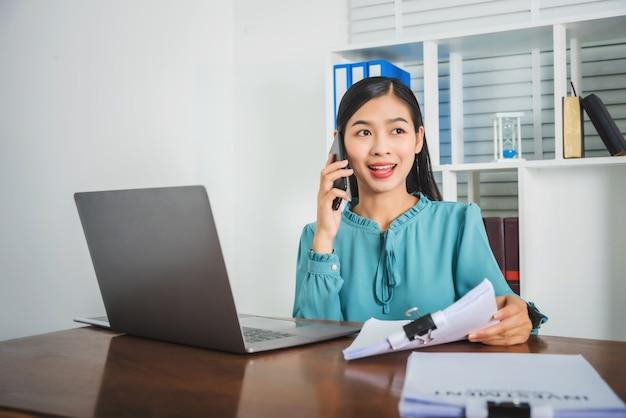 電話で話している間、オフィスで若い女性作業書類。