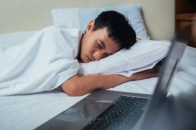 Усталый деловой человек спит в постели с ноутбуком.