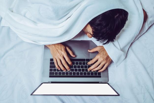 Усталый деловой человек, используя ноутбук в постели.