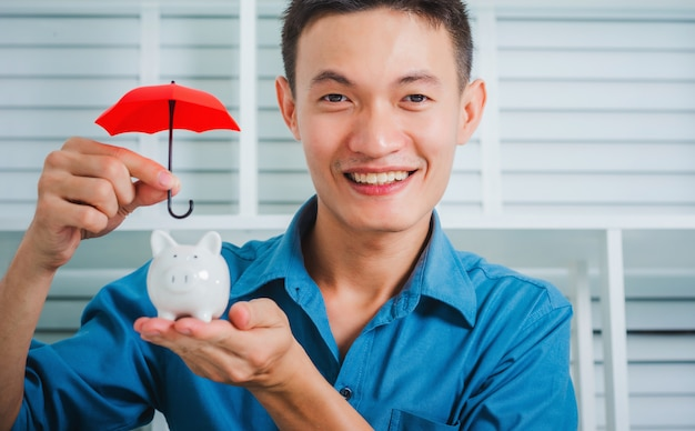 Молодой азиатский бизнесмен держа зонтик для копилки защиты.