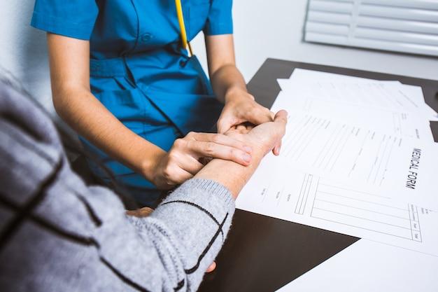 看護師は高齢患者の手首に脈拍ハンドルを使用する