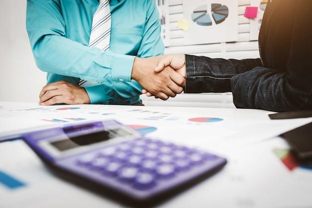 銀行家が家を借りるのを承認するために顧客と握手を交わす。