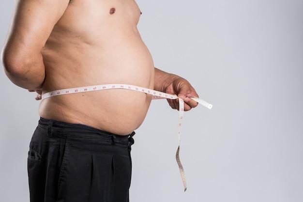 太った男は、測定テープで腹を測定しています