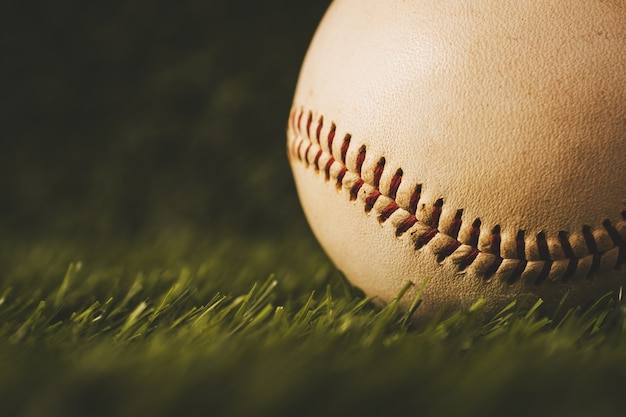 Бейсбол используется на фоне зеленой травы.