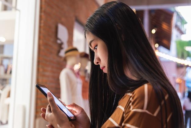 市内の携帯電話の新しいアプリの技術を保持している若い女の子。