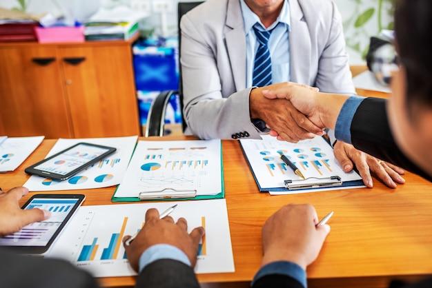 Коллеги делового партнера жмут друг другу руки на встрече в современном офисе обсуждая управление проектом.