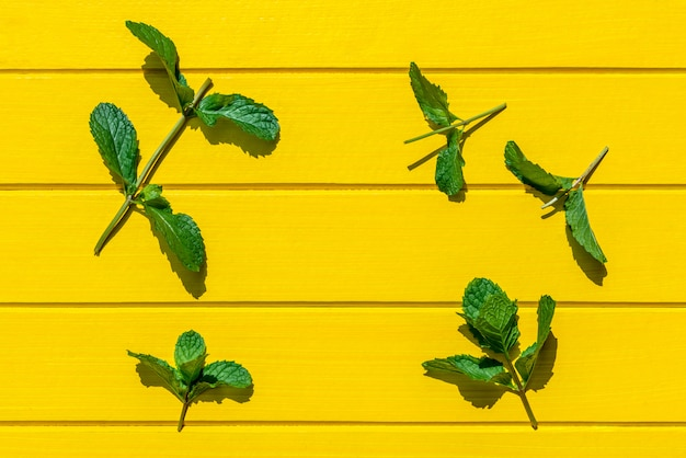 Листья свежей мяты изолированные на желтом цвете, взгляд сверху.