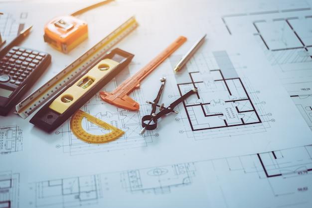 テーブルデスクに置かれた建築家図面計画オブジェクト。