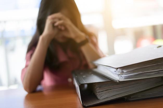 Утомленная коммерсантка работая с портативным компьютером.