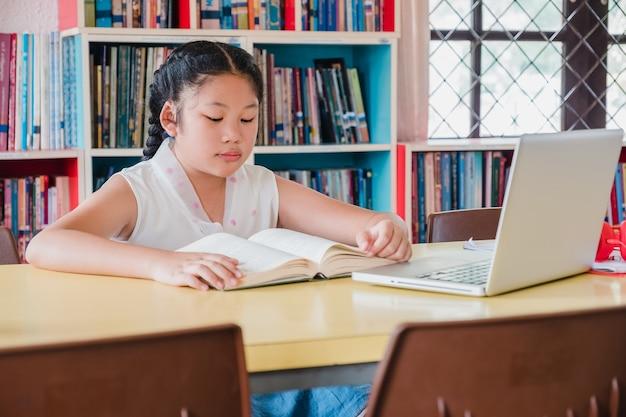 Девочка-подросток читает книгу с ноутбуком в библиотеке. концепция образования и грамотности