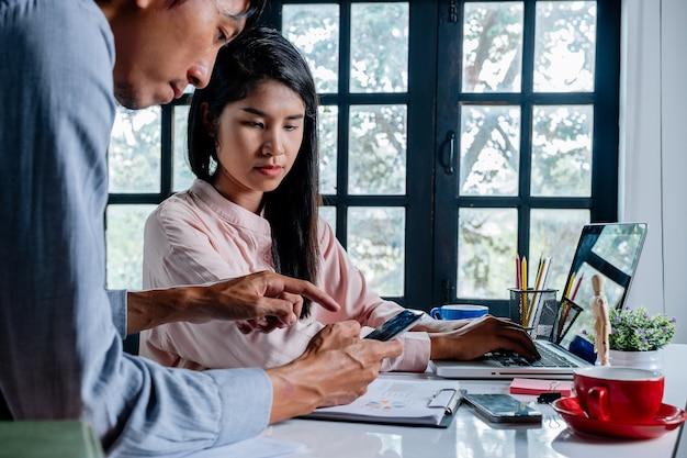 Два коллеги обсуждают данные со смартфоном и новым современным компьютерным ноутбуком на столе