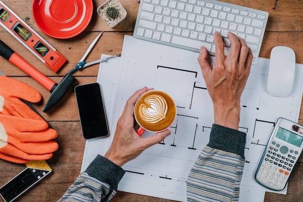Мужчина держит чашки кофе на деревенском деревянном столе стола. вид сверху