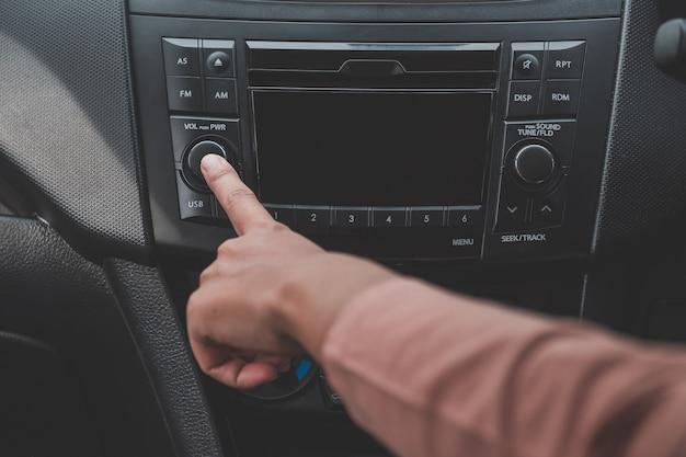 Женщина рукой включит радио на автомобиле для прослушивания музыки.