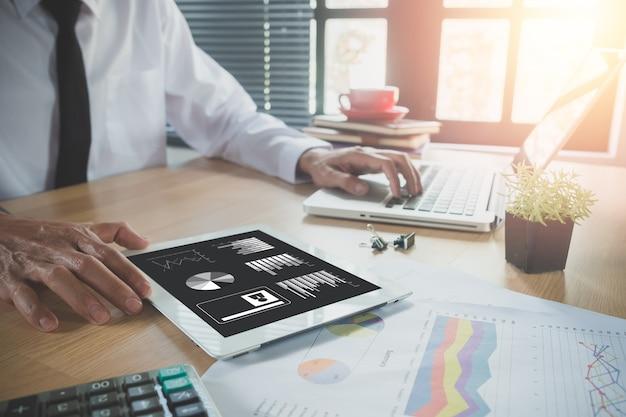 Бизнесмен, работающий с цифровым планшетом, книга и документ на деревянном столе в современных