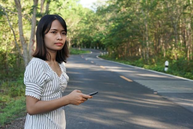 Азиатская женщина ждет автобус на обочине дороги