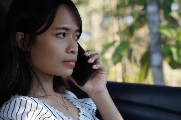 車の中で電話をしている女の人
