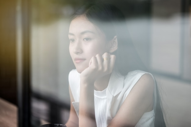 Задумчивый красивая молодая женщина, сидя за окном