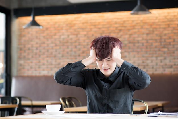 Деловой человек, сидя в депрессии с рукой на голове