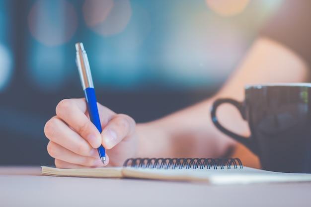 ビジネスの女性の手はペンでノートに書いています。