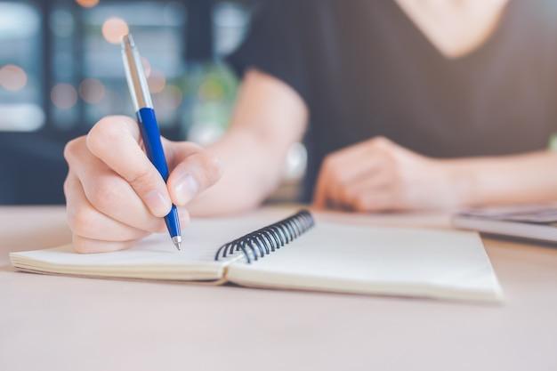 女性の手がペンでノートに書いています。