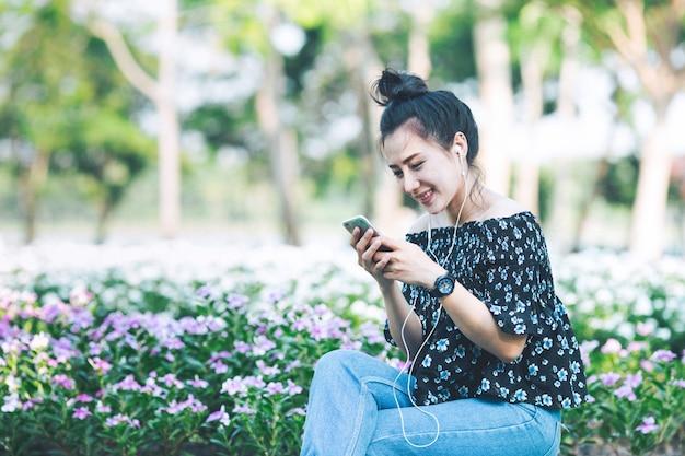 女性はスマートフォンを保持しているとヘッドフォンで音楽を聴いています