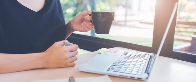 女性の手は、オフィスでラップトップコンピューターを使用しています。