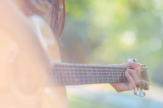 女性の手は庭でアコースティックギターを弾いています。