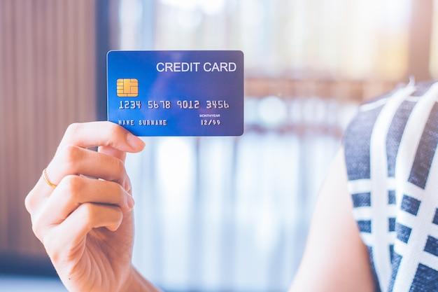 ビジネスの女性の手は青いクレジットカードを保持しています。