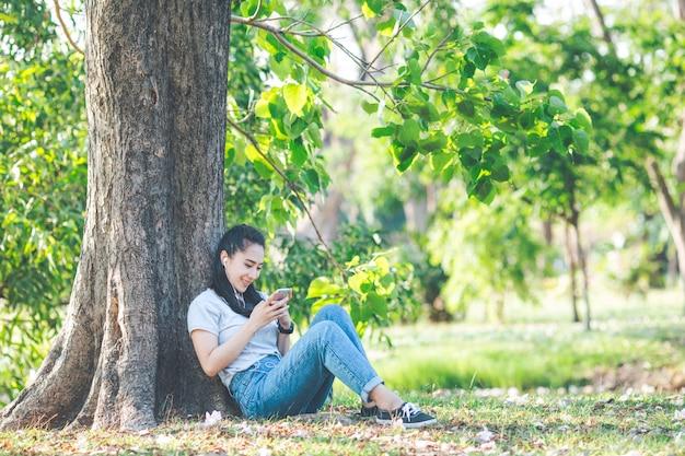 女性は音楽を聴き、木々の下でリラックスします。