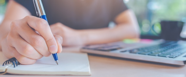 オフィスでペンでメモ帳に書く婦人